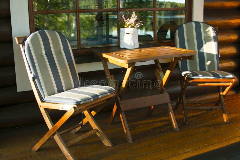 Tavola e sedie di legno della mobilia al tramonto fotografia stock