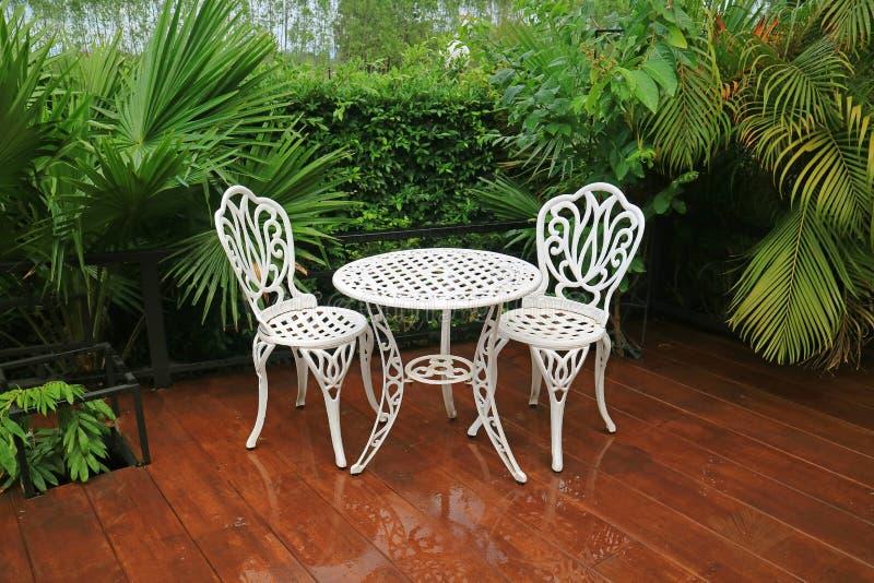 Tavola e sedie di tè bianche vuote del giardino del ferro battuto nel patio dopo pioggia immagine stock libera da diritti