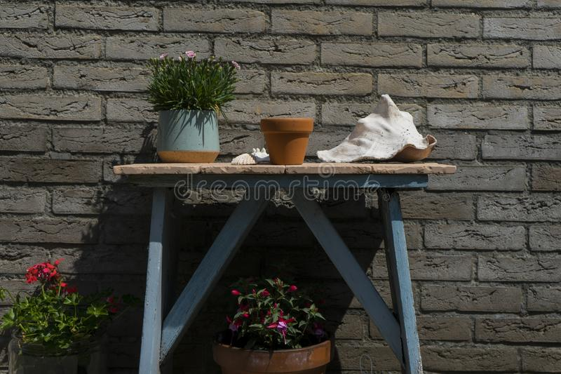 Tavola minimalistic astratta della decorazione del giardino Con il fondo del mattone della casa ed i piccoli vasi della pianta in immagine stock