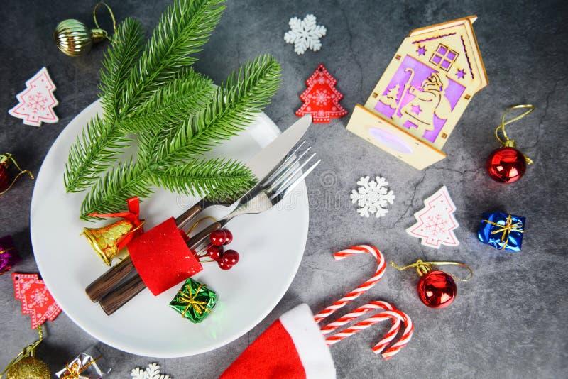 Tavola natalizia ambientata la decorazione con scatola regalo una canna da zucchero candela a santa claus cappello forchetta e la fotografie stock libere da diritti