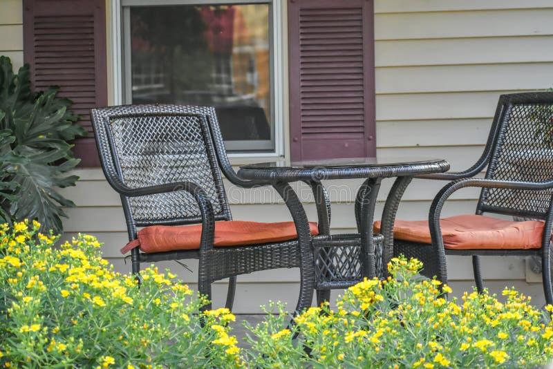 Tavola Patio e sedie con fiori gialli immagine stock libera da diritti