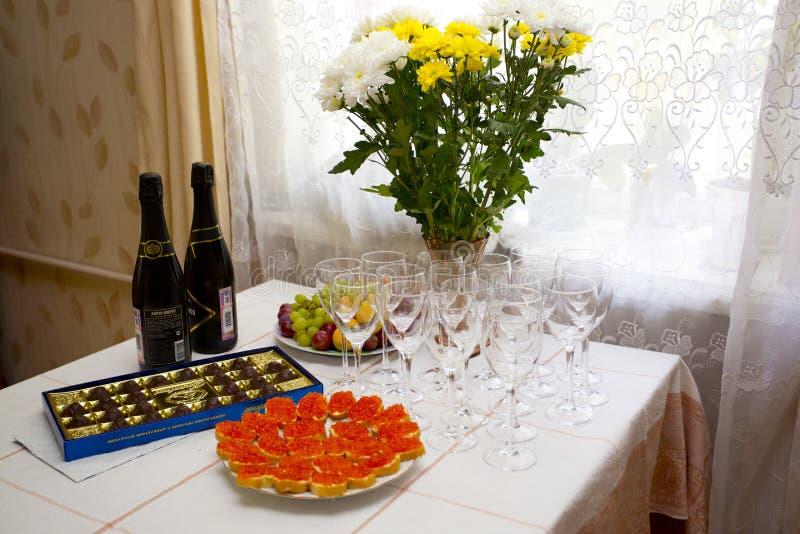 Tavola posta con il cioccolato, i panini con il caviale ed i vetri di champagne immagini stock