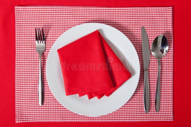 Tavola posta - la forchetta ed il cucchiaio hanno messo sul panno rosso ed il piatto bianco fotografia stock