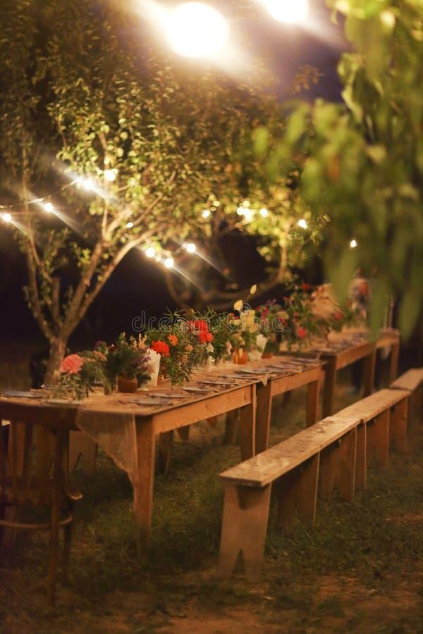 Tavola pronta per una cena all'aperto rustica alla notte con le lampade fotografia stock libera da diritti