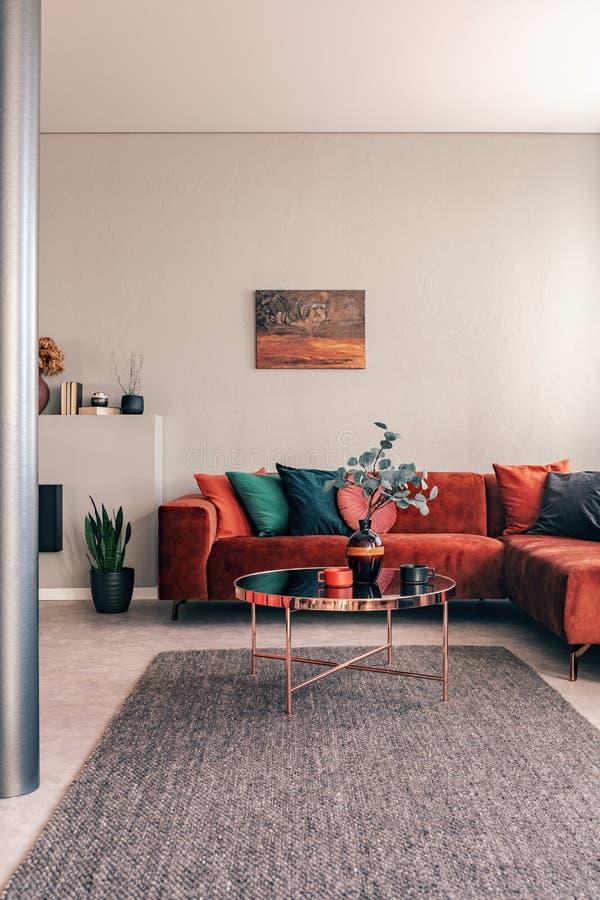 Tavola rotonda alla moda con i fiori accanto al sofà d'angolo con i cuscini verde smeraldo immagine stock
