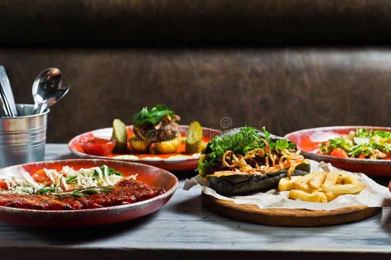 Tavola servita con i vari piatti del ristorante Hot dog, costole di carne di maiale del barbecue, bistecca, pasta di Carbonara ed immagine stock