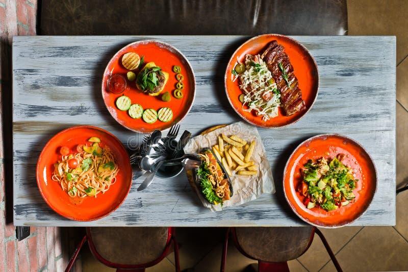 Tavola servita con i vari piatti del ristorante Hot dog, costole di carne di maiale del barbecue, bistecca, pasta di Carbonara ed fotografie stock