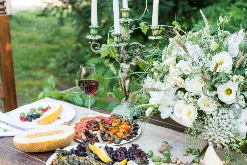 Tavola servita con il melone, le verdure arrostite, il vetro di vino rosso e la frutta fotografie stock