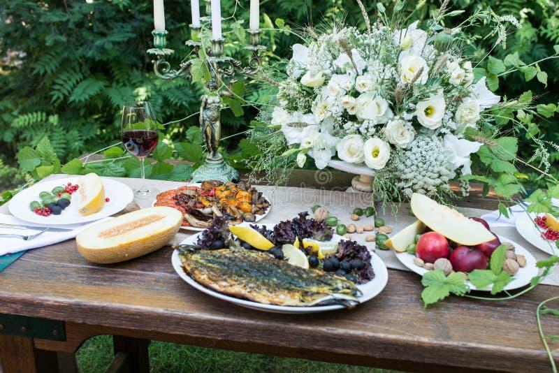 Tavola servita con vetro di vino rosso e dei frutti, melone, verdure arrostite, fotografia stock