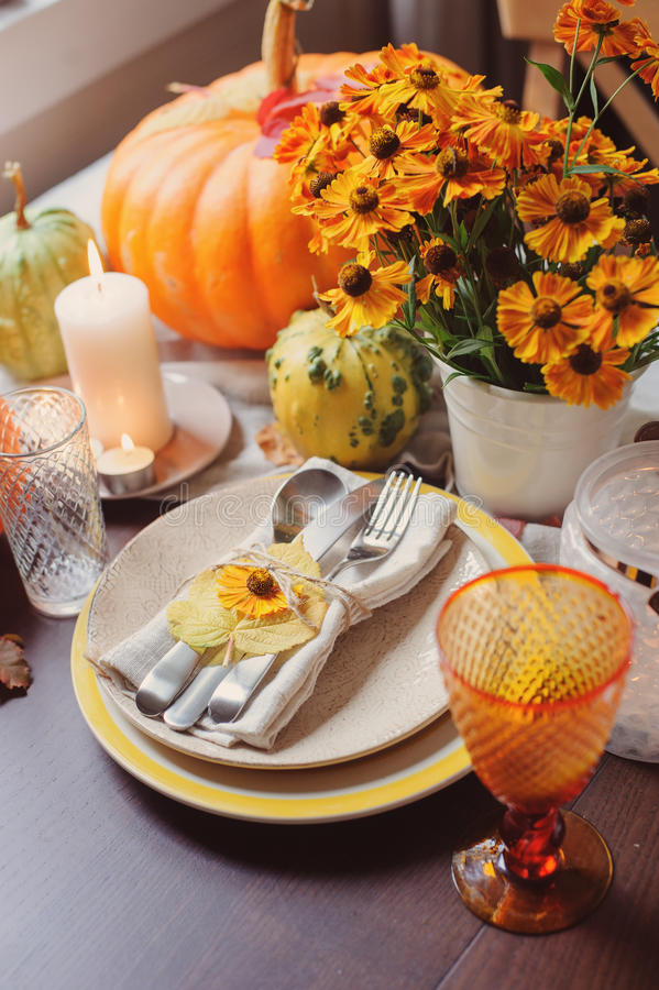 Tavola stagionale tradizionale di autunno che mette a casa con le zucche, le candele ed i fiori immagini stock