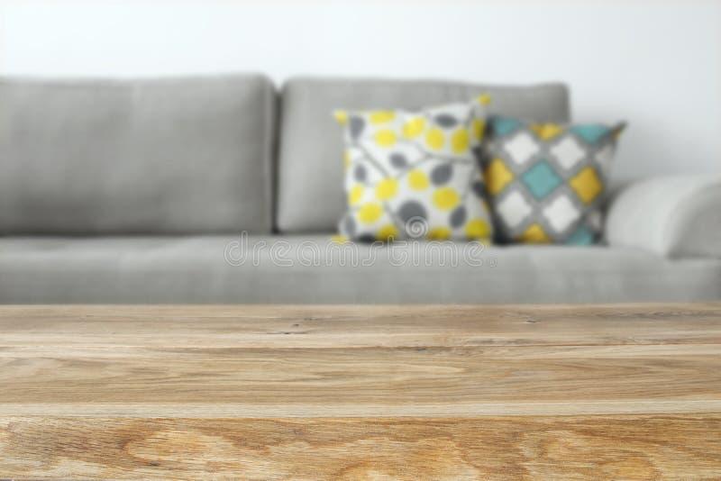 Tavola vuota di legno davanti all'interno del sofà del salone fotografia stock