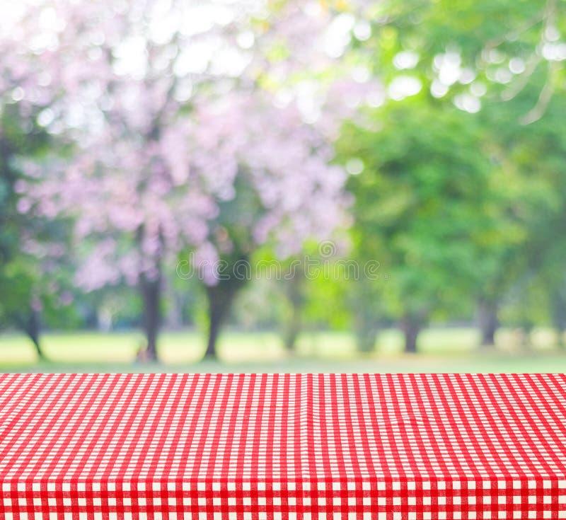 Tavola vuota e tovaglia rossa con il bokeh delle foglie verdi della sfuocatura, per fotografia stock libera da diritti