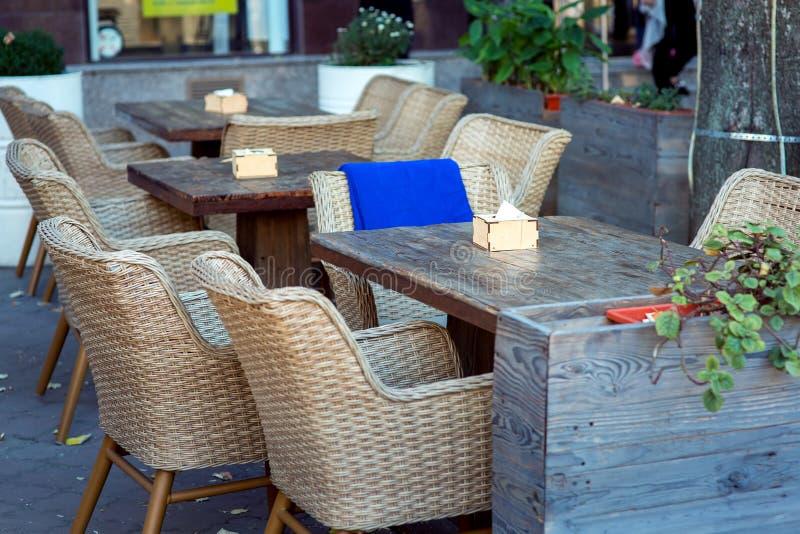 Tavole di legno e sedie di vimini immagini stock