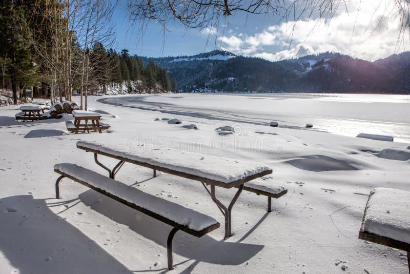 Tavole di picnic innevate dal lago congelato fotografie stock