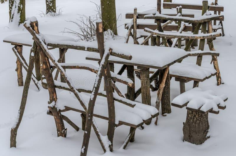 Tavole e sedie di legno - mobilia per un picnic fatto a mano, supporto fra il legno innevato sparso con neve fotografia stock libera da diritti