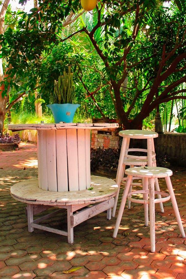 Tavole e sedie di legno sotto un albero fotografie stock