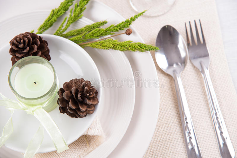 Tavolo da pranzo che mette piatto bianco con le candele, fiore, annata c fotografie stock libere da diritti
