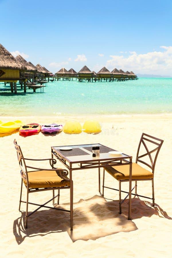 Tavolo da pranzo con due sedie sulla spiaggia sabbiosa dal mare tropicale fotografie stock