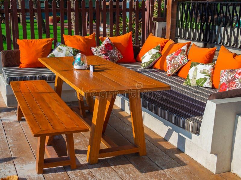 Tavolo da pranzo con la sedia lunga di legno e cuscini arancio sul sofà moderno sul pavimento di legno fotografia stock libera da diritti