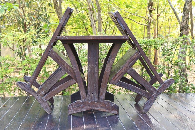 Tavolo da pranzo di legno messo nella regolazione del giardino fertile fotografia stock