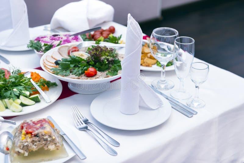 Tavolo da pranzo festivo servito con i piatti, spuntini, insalate, vetri immagine stock libera da diritti