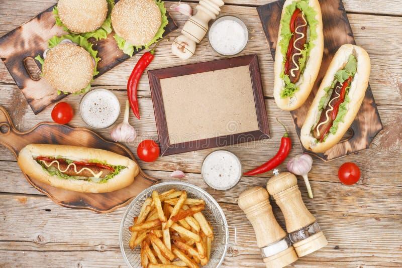 Tavolo da pranzo il giorno di hot dog con lo spazio della copia Alimenti a rapida preparazione, hot dog, chip, patate fritte, bir immagini stock libere da diritti