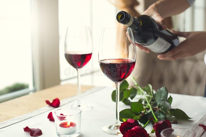 Tavolo da pranzo in vetri di vino del primo piano del ristorante che versano alcool immagine stock