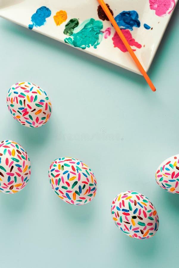 Tavolozza multicolore divertente delle uova di Pasqua delle pitture e della spazzola di arte, su fondo blu molle immagine stock