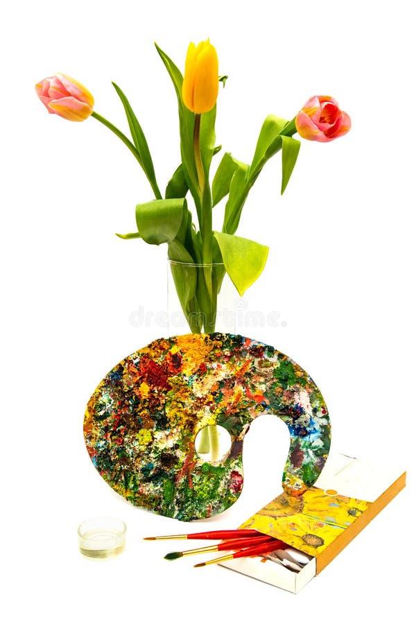 Tavolozza variopinta della pittura a olio con una spazzola Pennelli e pitture per disegnare Tulipani su una priorità bassa bianca fotografie stock