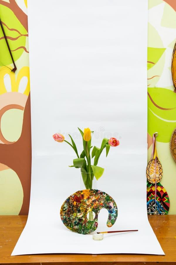 Tavolozza variopinta della pittura a olio con una spazzola Pennelli e pitture per disegnare Tulipani su una priorità bassa bianca fotografia stock