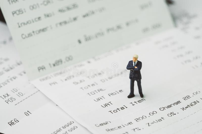 Tax, accounting and business expenses concept, miniature businessman figure standing on printed payment invoice or receipt around royalty free stock photos