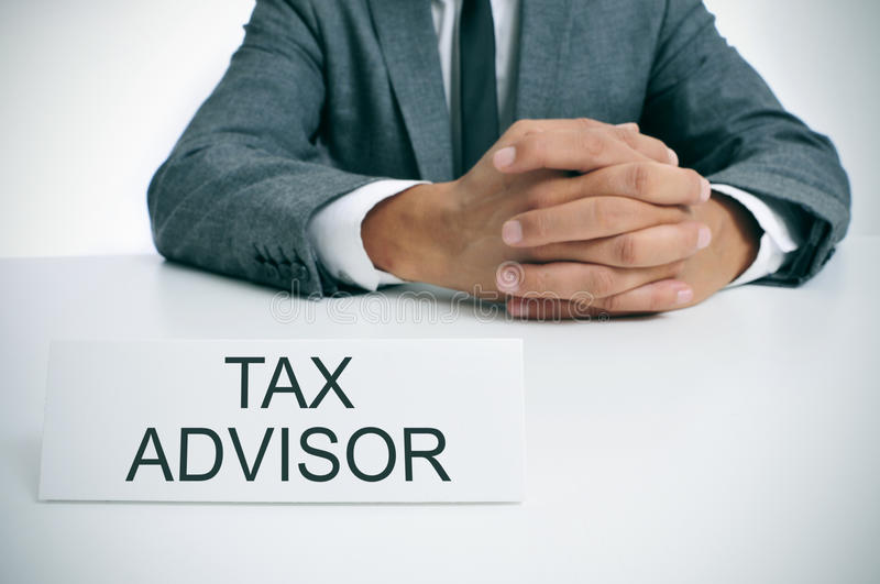 Tax advisor at the office. A man wearing sitting at his office desk with a signboard in front of him with the text tax advisor stock image