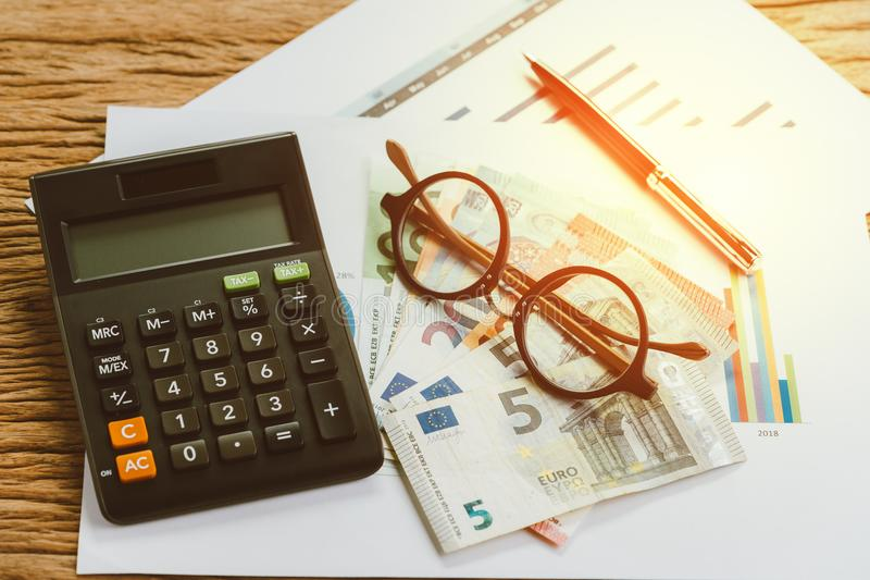 Tax calculation or budget planning concept, eyeglasses, pen on p. Ile of Euro banknotes on graph and chart performance print paper and calculator on wood table stock photography