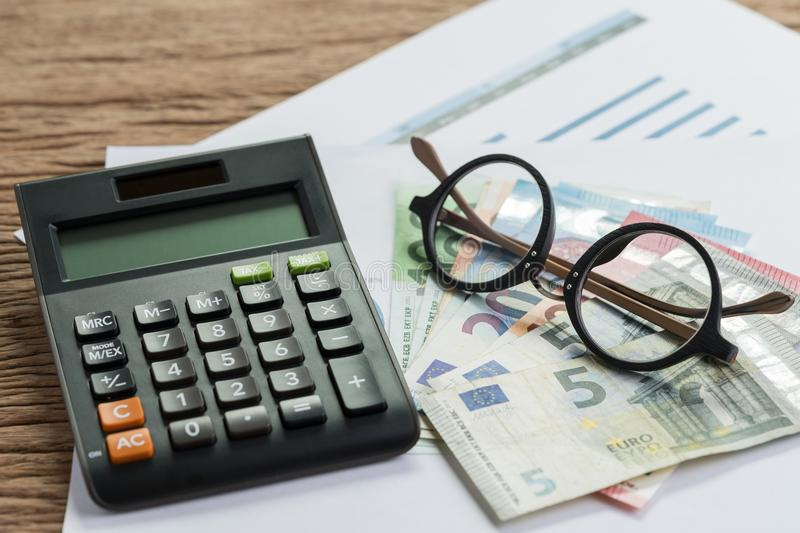 Tax calculation or budget planning concept, eyeglasses on pile o. F Euro banknotes on graph and chart performance print paper and calculator on wood table royalty free stock images
