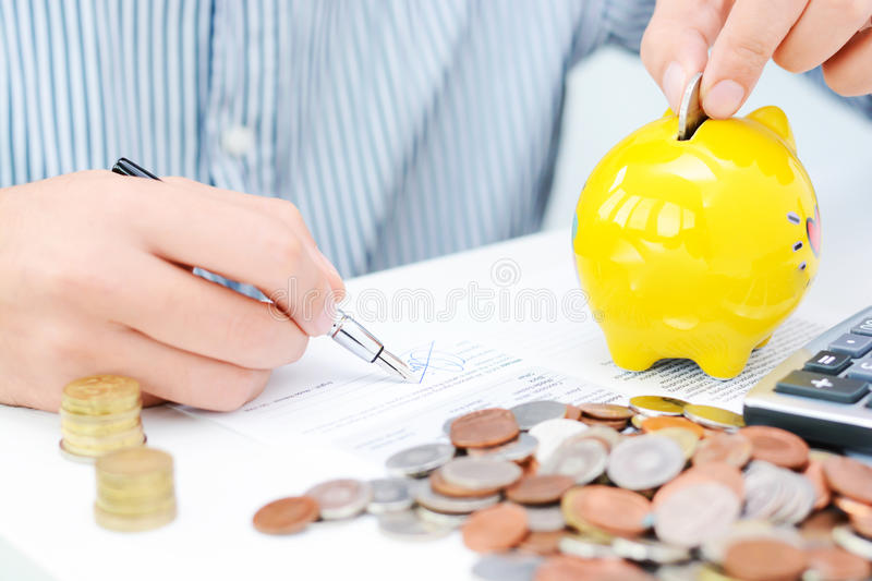 Tax calculation or new loan agreement with calculator and coins. Tax calculation or loan agreement with hand calculator and coins stock photos