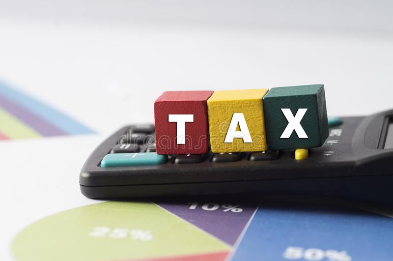 Tax Concept with colorful wooden block tax word on calculator royalty free stock photo