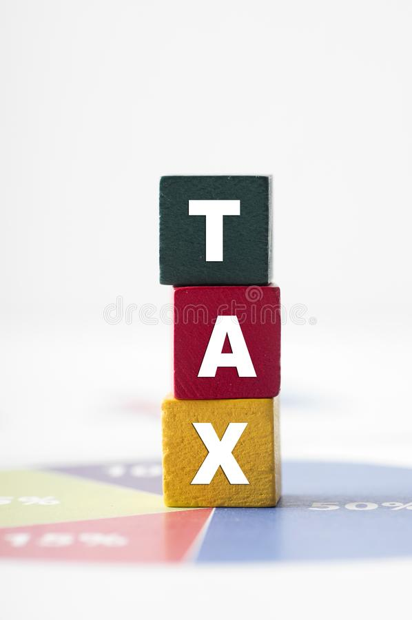 Tax Concept with colorful wooden block tax word on pie chart stock photo
