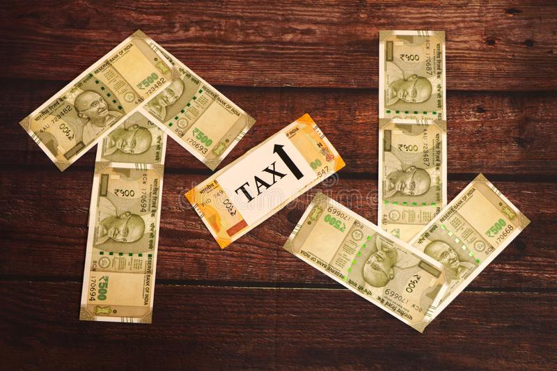 Tax concept. Indian Currency showing ups and down. Tax concept. Indian Currency showing ups and down of tax royalty free stock photos