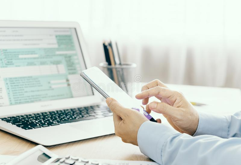 Tax concept. Accountants are filling online tax information using smart phones stock photography
