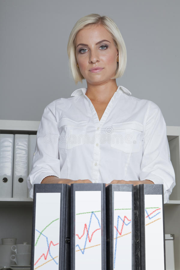 Tax consultant with four folders. Tax counsellor with four folders showing her economical success stock photo