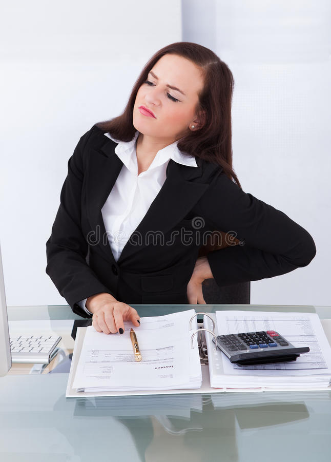Tax consultant suffering from backache at desk. Young female tax consultant suffering from backache sitting at desk in office royalty free stock images