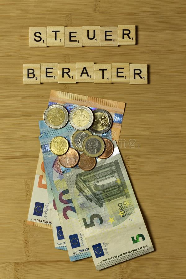 Tax consultant word in german Steuerberater. Euro banknotes on the table stock photo