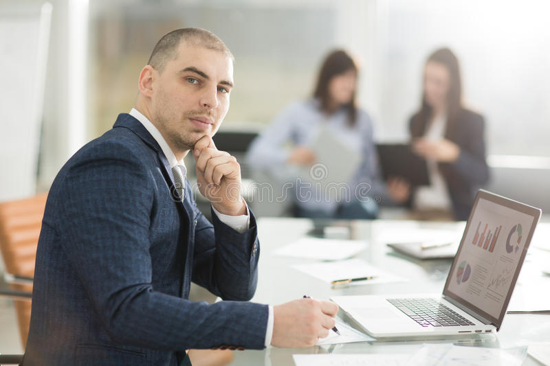 Tax consultant works with financial charts at the workplace. In the office royalty free stock image
