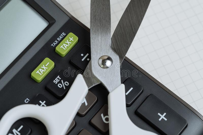 Tax cut, budget reduction, debt cutout concept, white scissors on black calculator with green button with tax minus and tax plus. Label on grid line paper note stock images