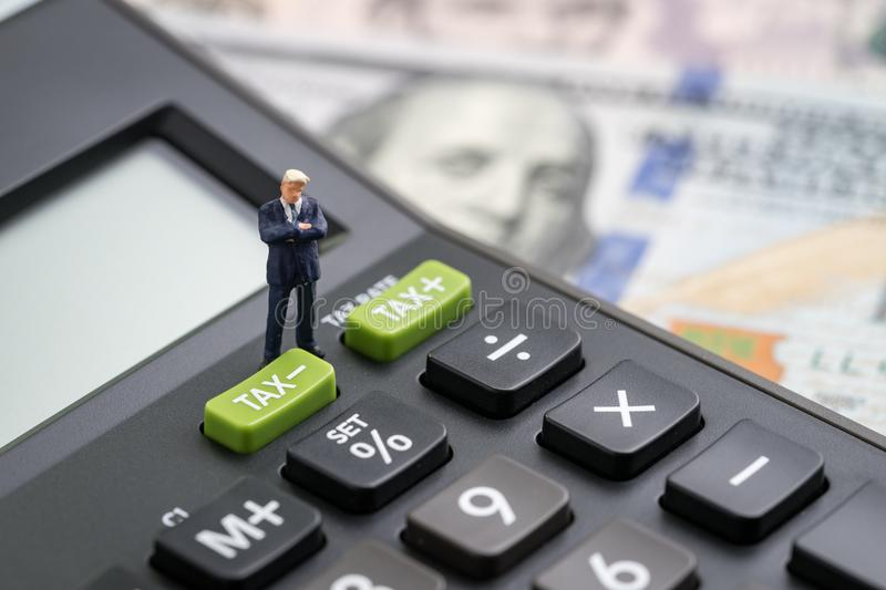 Tax cuts or reduce concept, miniature people business man president standing with TAX minus button on calculator with background stock photos