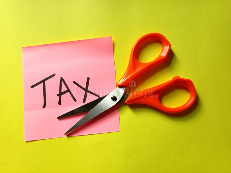 Tax cut bill and scissors on yellow background royalty free stock photo