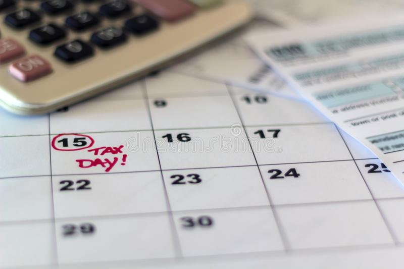 Tax day marked on calendar, calculator and tax form. On desk stock images