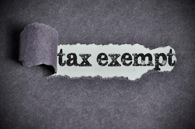 Tax exempt word under torn black sugar paper.  stock images