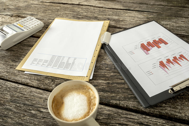 Tax and finance concept. Paperwork with graphs, charts, data and numbers, adding machine and a cup of fresh hot cappuccino on a textured rustic wooden desk stock image
