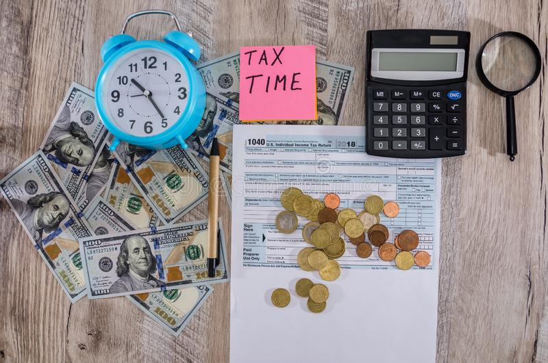 Tax form 1040, alarm clock, dollars, calculator and coins. Close-up. View from above. Tax form 1040, alarm clock, dollars, calculator and coins royalty free stock image
